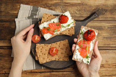 Woman eating fresh rye crispbreads with salmon, cream cheese and tomatoes at wooden table, top view