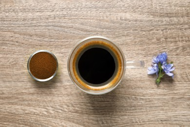 Glass cup of delicious chicory drink, powder and flowers on wooden table, flat lay