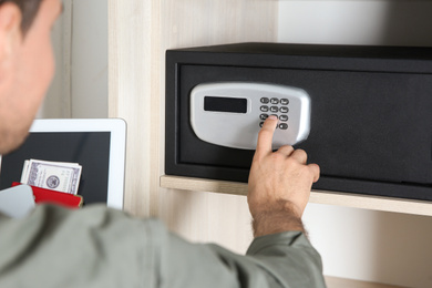 Man opening black steel safe with electronic lock at hotel, closeup