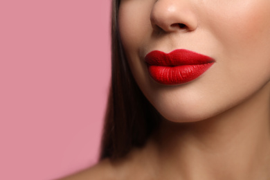 Woman with red lipstick on pink background, closeup