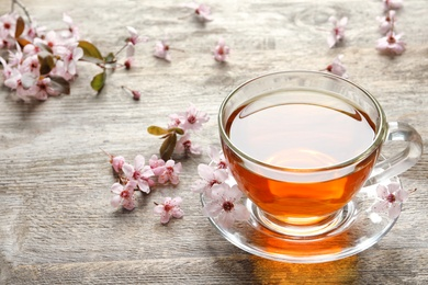 Cup of tea and blossoming flowers on wooden background