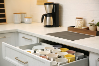 Open drawer with cups and coffeemaker on countertop in kitchen