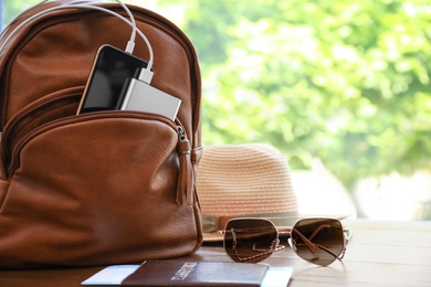 Sunglasses, passport, hat and backpack with gadgets on wooden table, space for text. Charging electronics during travel