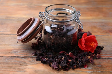 Dry hibiscus tea and flower on wooden table