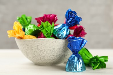 Candies in colorful wrappers on white wooden table, closeup