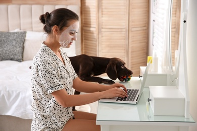 Young woman with facial mask working on laptop near her playful dog in home office