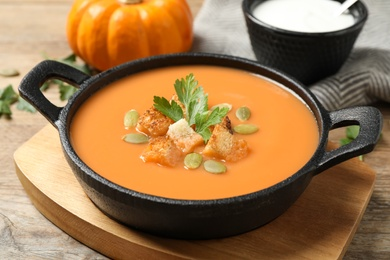 Tasty creamy pumpkin soup with croutons, seeds and parsley in bowl on wooden table