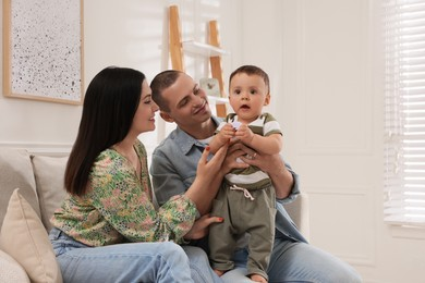Portrait of happy family with little child at home