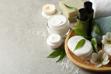 Spa composition with skin care products on textured table, closeup. Space for text