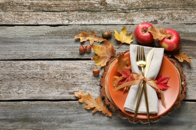 Festive table setting with autumn decor and apples on wooden background, flat lay. Space for text