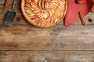 Flat lay composition with delicious homemade apple tart on wooden table. Space for text