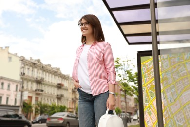 Young woman waiting for public transport at bus stop