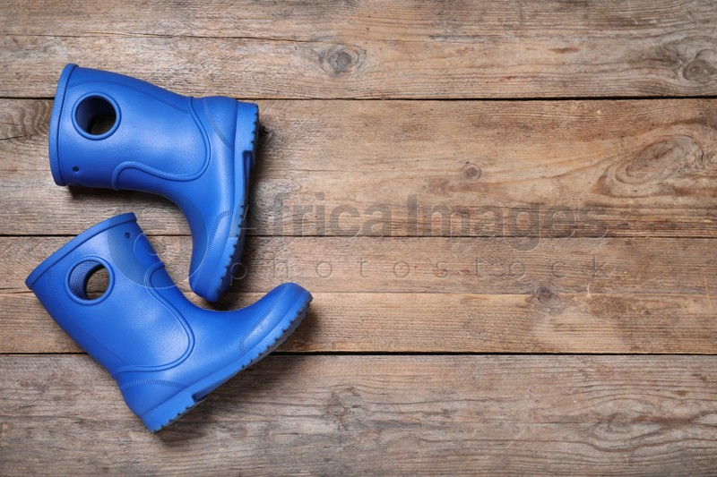 Blue rubber boots on wooden background, top view. Space for text