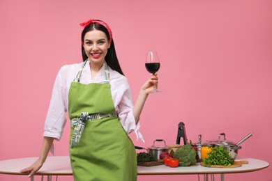 Young housewife with glass of wine, vegetables and different utensils on pink background. Space for text