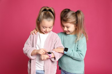 Little girls with smart watches on pink background
