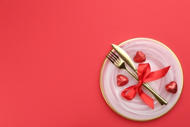 Beautiful table setting on red background, top view with space for text. Valentine's Day dinner