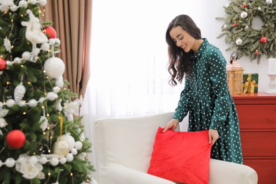 Woman putting decorative pillow on armchair at home