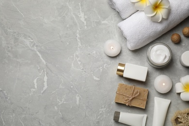 Flat lay composition with towels and skin care products on light grey marble background, space for text