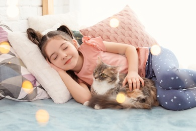 Cute little girl with cat lying on bed at home