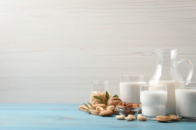 Different nut milks on light blue wooden table. Space for text