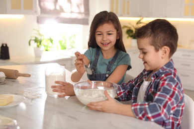 Cute little children cooking dough in kitchen at home