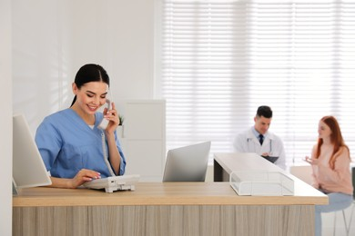 Receptionist talking on phone while doctor working with patient in hospital