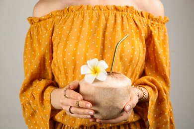Woman holding fresh young coconut with straw on grey background, closeup