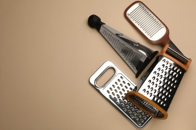 Different modern graters on beige background, flat lay. Space for text