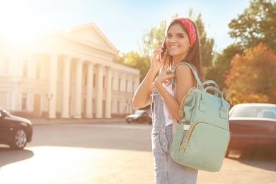 Young woman with stylish turquoise bag talking on phone outdoors