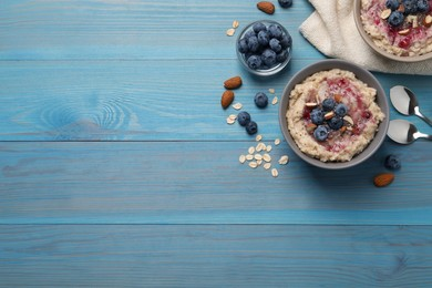 Tasty oatmeal porridge with toppings on light blue wooden table, flat lay. Space for text