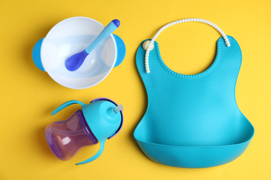 Set of colorful plastic dishware and silicone bib on yellow background, flat lay. Serving baby food