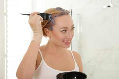 Young woman applying hair dye on roots in bathroom