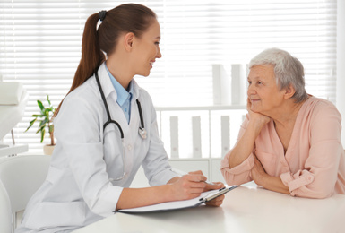 Doctor examining senior patient in modern office