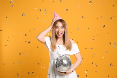 Happy young woman in party hat with disco ball and confetti on yellow background