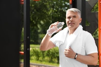 Handsome mature man with bottle of water on sports ground. Healthy lifestyle