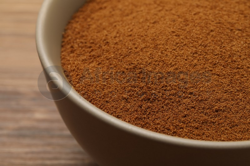 Bowl of chicory powder on wooden table, closeup