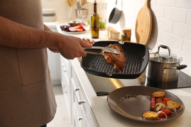Man taking cooked tasty meat from frying pan, closeup