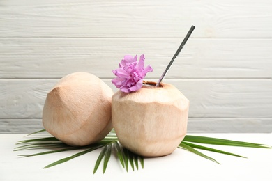 Young peeled coconuts with straw, palm leaf and flower on white wooden table