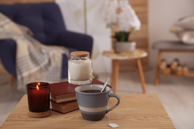 Cup of tea, books and candles on wooden table in living room. Interior design