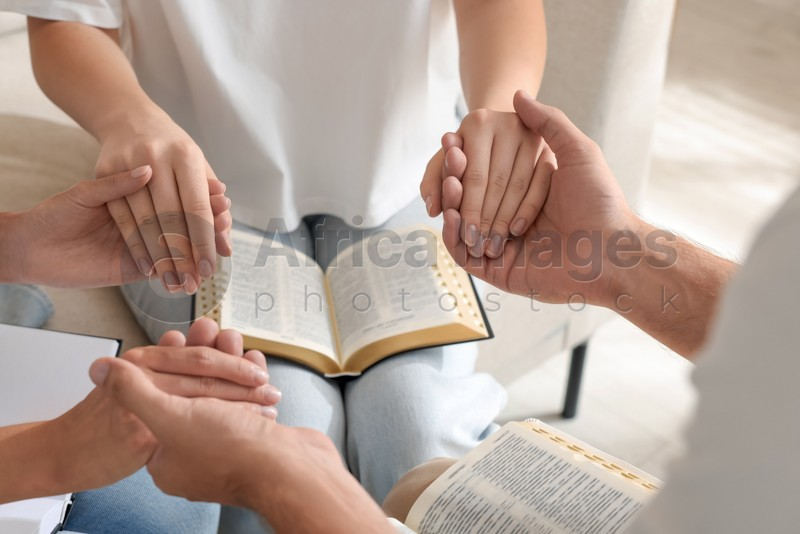 Group of religious people with Bibles holding hands and praying together indoors, closeup