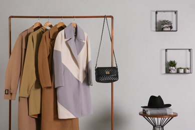 Different warm coats on rack in stylish room interior
