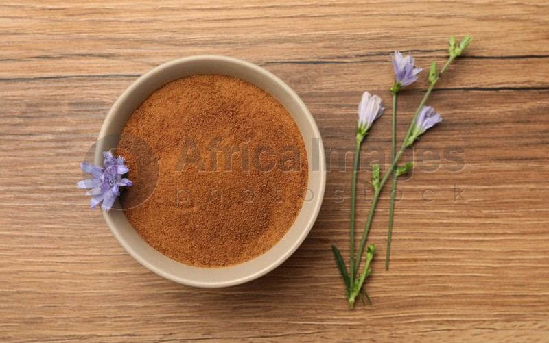 Bowl of chicory powder and flowers on wooden table, flat lay