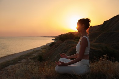 Mature woman meditating on hill near sea at sunset. Space for text