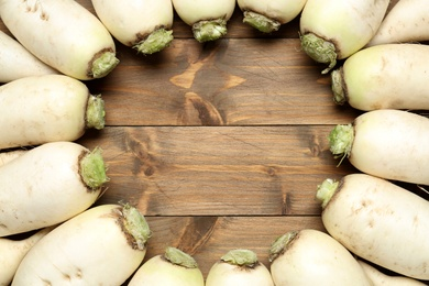 Frame of white turnips on wooden table, flat lay. Space for text