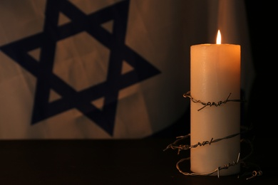Barbed wire and burning candle on black background. Holocaust memory day