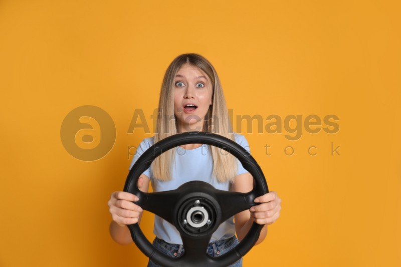 Emotional young woman with steering wheel on yellow background