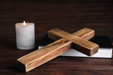 Cross, Bible and burning candle on wooden background, closeup. Christian religion