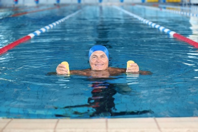 Sportive senior man doing exercises in indoor swimming pool