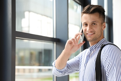 Male business trainer talking on phone in office