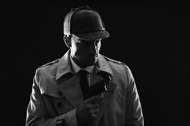 Old fashioned detective with revolver on dark background, black and white effect